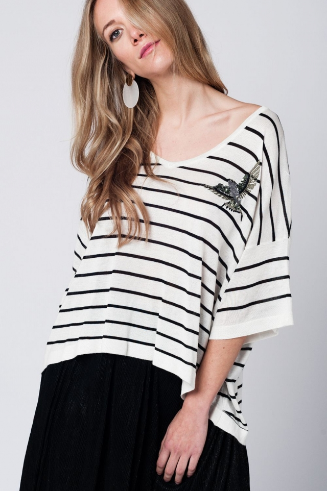White sweater with black stripes and bird detail on the front