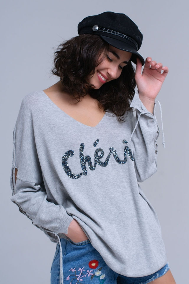 Gray sweater with slogan and ribbons