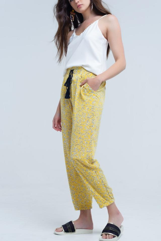 Gelbe Hose mit bedruckten Blättern und Taschen