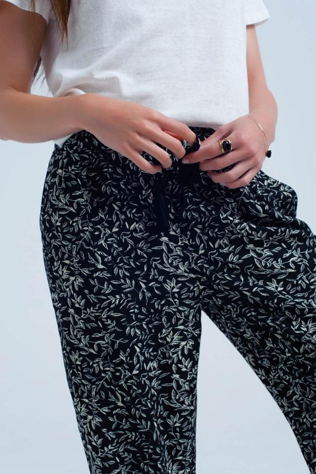 Schwarze Hose mit bedruckten Blättern und Taschen