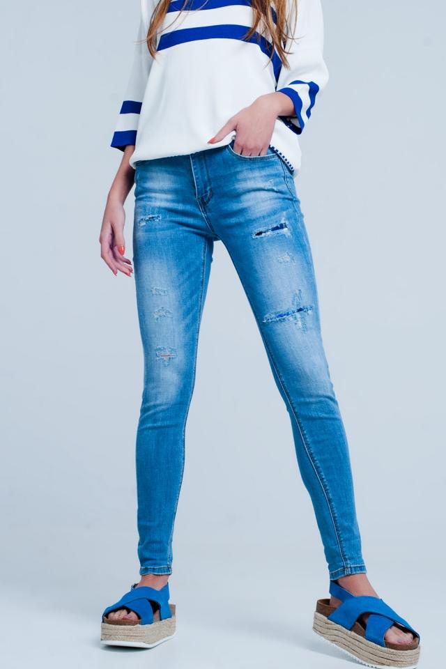 Schmale Stretch-Jeans mit Rissen und Flicken in Mittelblau