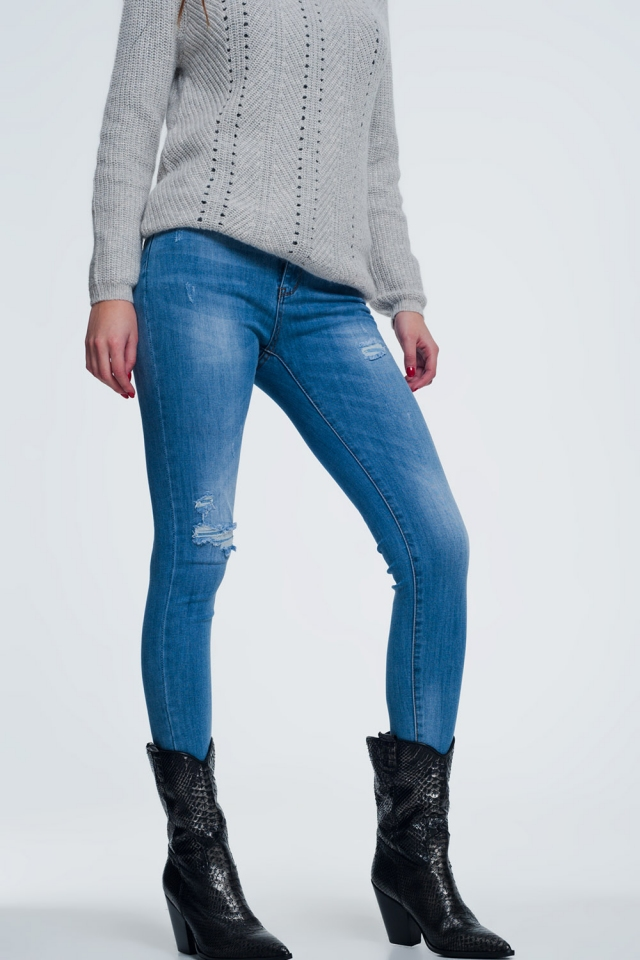 Light denim skinny jeans with one ripped knee