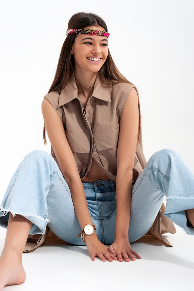 Sleeveless beige shirt with shoulder pads and utility pockets