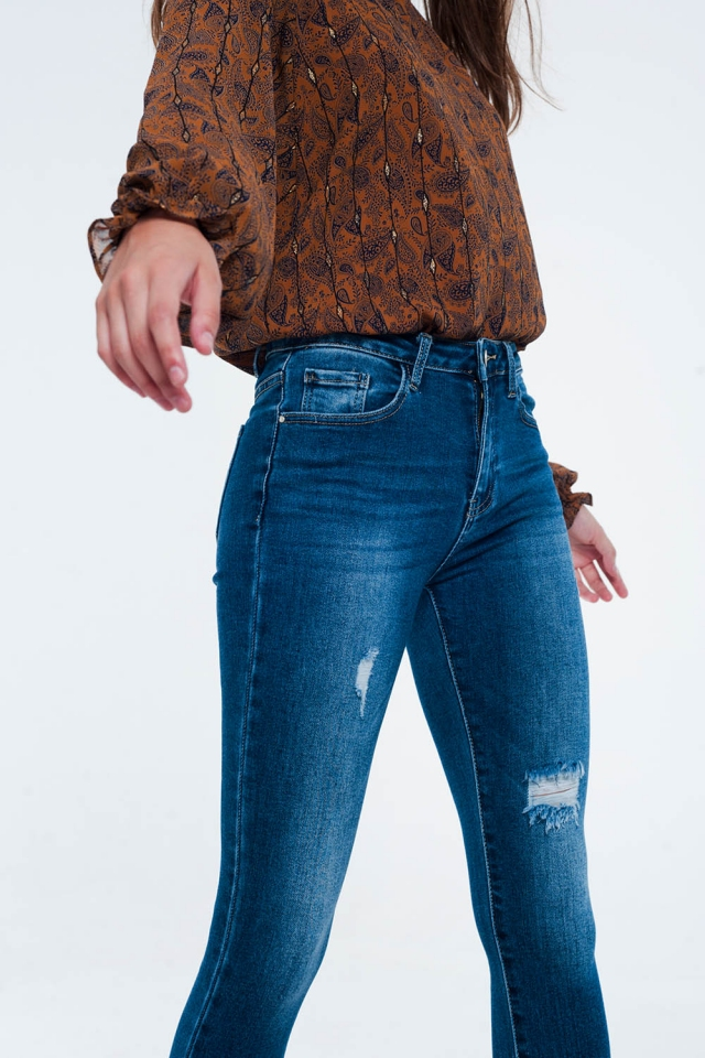 skinny jean with chewed hem and distressing in mid blue
